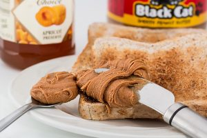 peanut butter on a knife being put on toast