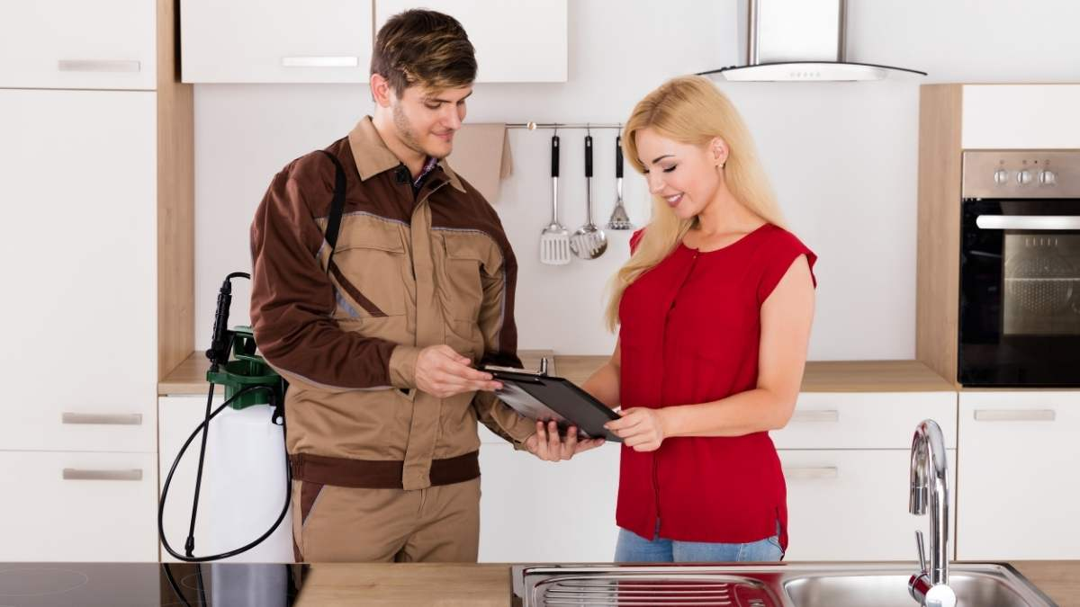 pest control technician speaking with lady